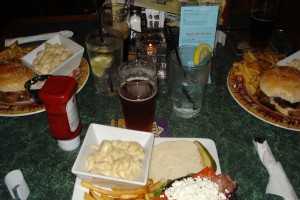A picture of plates of food and beer - sandwiches and macaroni and cheese.