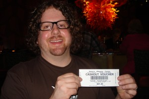 A picture of a man with long curly hair, a beard and glasses holding up a white ticket with a cash sum printed on it.
